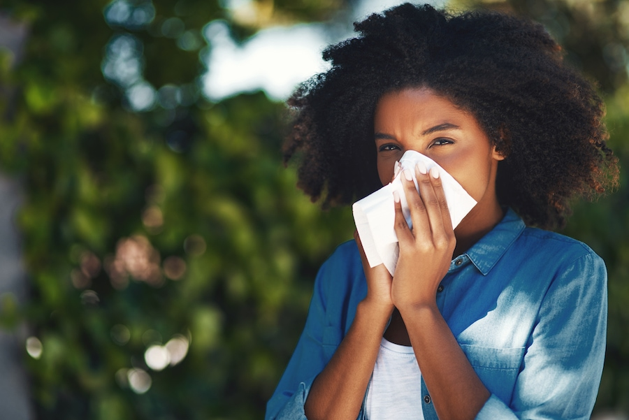 Woman blowing her nose due to seasonal allergies and not having clean AC unit