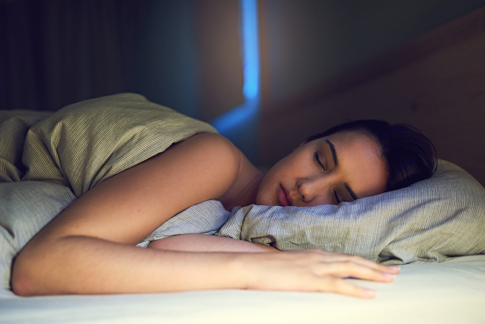 Woman sleeping comfortably due to using AC in home at night