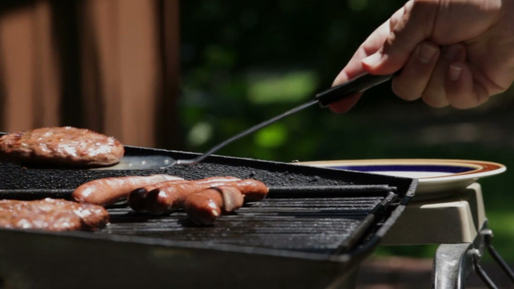 Energy saving tip to cook outside showing man grilling in yard