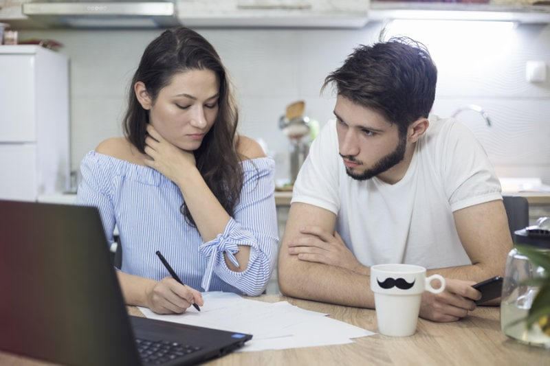 couple sitting by computer trying to figure out if HVAC preventative maintenance is worth it for their home