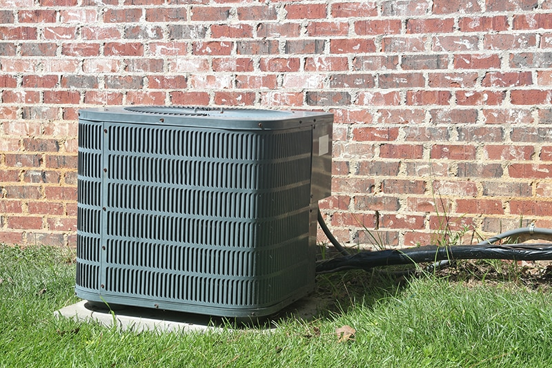 top causes of air conditioner failure, home ac unit sitting in front of a brick wall