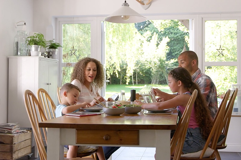 Indoor Air Quality Affects Your Family's Health, family of four eating together in naturally lit dining room at home